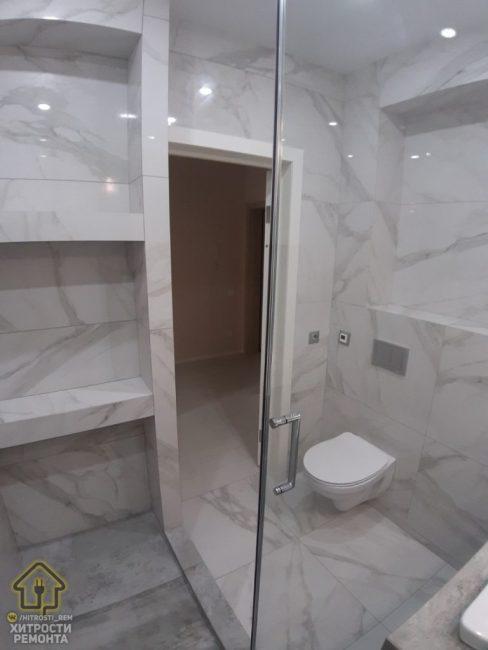 Так выглядит вход в ванную комнату, если смотреть из душевой кабины. Как видите, все сделано под мрамор.