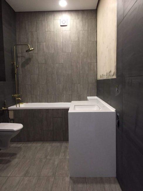Даже ванную он выложил серой плиткой. Потолок обшил пластиком. Освещением служат встроенные точечные светильники.