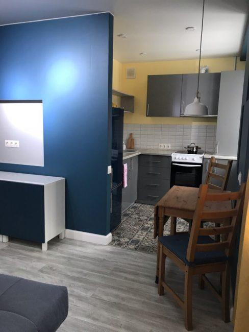 Так выглядит вход на кухню. Ее сделали в серых оттенках, добавив желтого цвета. Размер кухни небольшой, но для одного или двух человек подойдет.