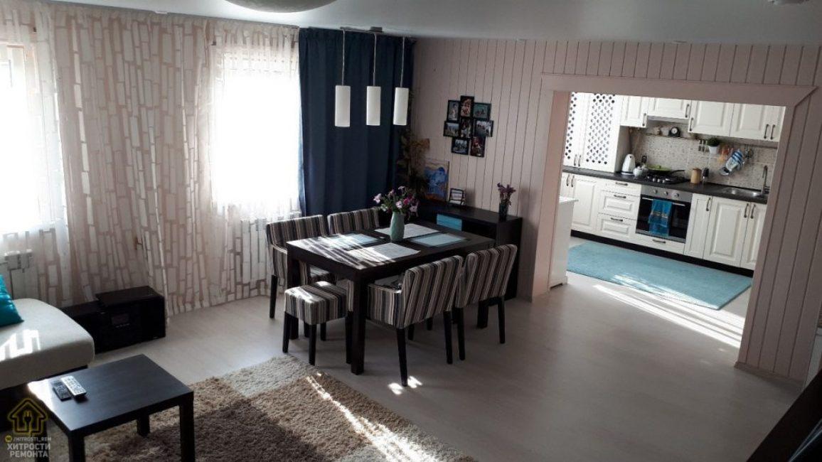 В гостиной все также выполнено в светлых теплых оттенках. В одной ее части выделили место под зону для столовой, куда поставили стол, 4 стула в полосатых чехлах и один табурет.