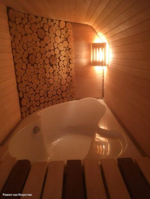 В другом углу расположилась ванная. Стена возле нее сделана из пеньков дерева. Такой декор в сауне выглядит очень актуально. В углу еще один светильник.
