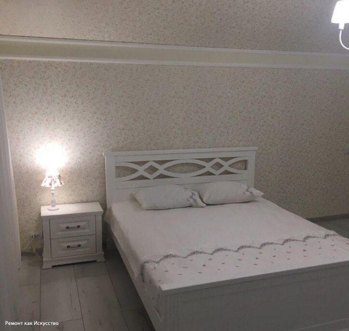Ближе к окну поставили белую двуспальную кровать и прикроватную тумбочку. На ней — лампа для чтения.