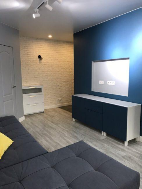 Одну из стен в гостиной сделали яркого синего цвета. Именно на ней в нише в будущем будет располагаться плазма.