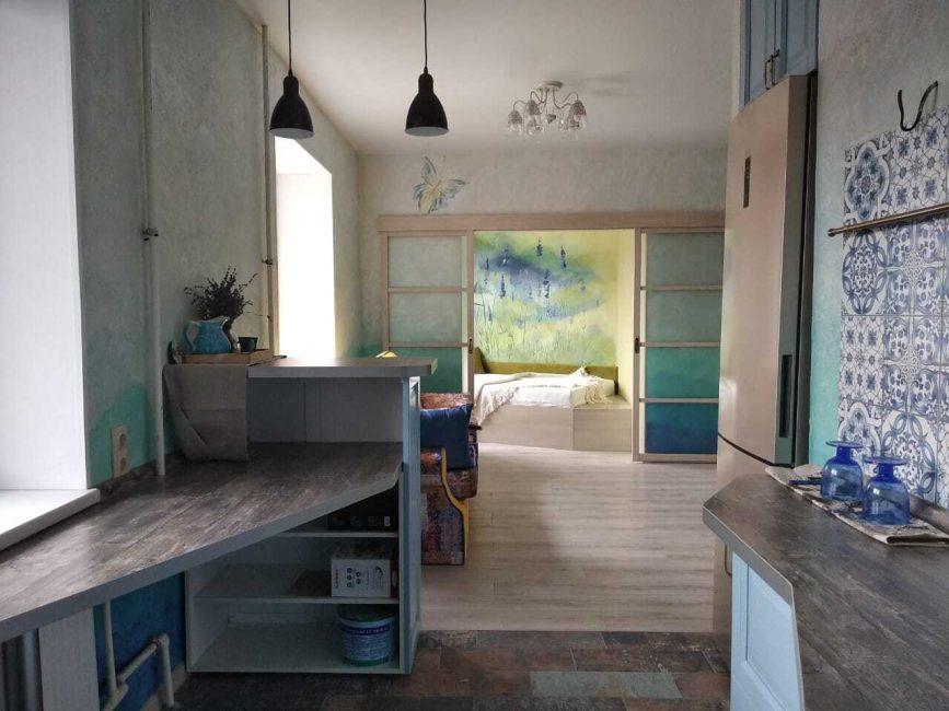 Вид из кухни. Сразу за залом — двери в спальню. Как видите, абсолютно каждая комната сделана в стиле прованс. В спальне на всю стену нарисован куст лаванды.