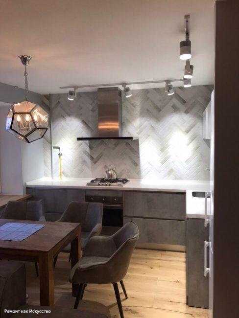 Оригинальности добавляют люстра над обеденным столом и плитка, которой выложили стену за варочной поверхностью
