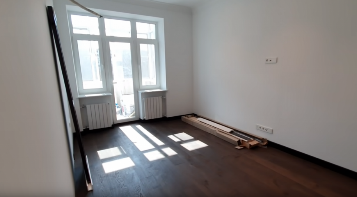 Стены сделаны под покраску. Вся мебель будет темной. Светильники точечные, в центре комнаты планируют повесить большую люстру. На полу плинтус и ламинат.