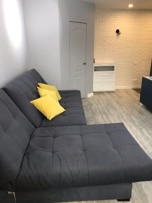 Практически все пространство в зале занимает удобный мягкий диван графитового цвета. Он раскладывается в полноценное двухместное спальное место.