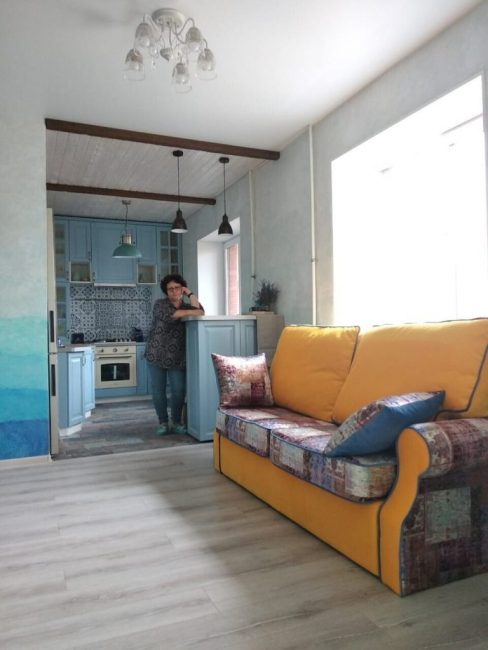 Оригинальным и ярким акцентом стал мягкий маленький диванчик в гостиной. часть его яркого апельсинового цвета, а часть будто сделана в стиле печворк, из старых одеял.