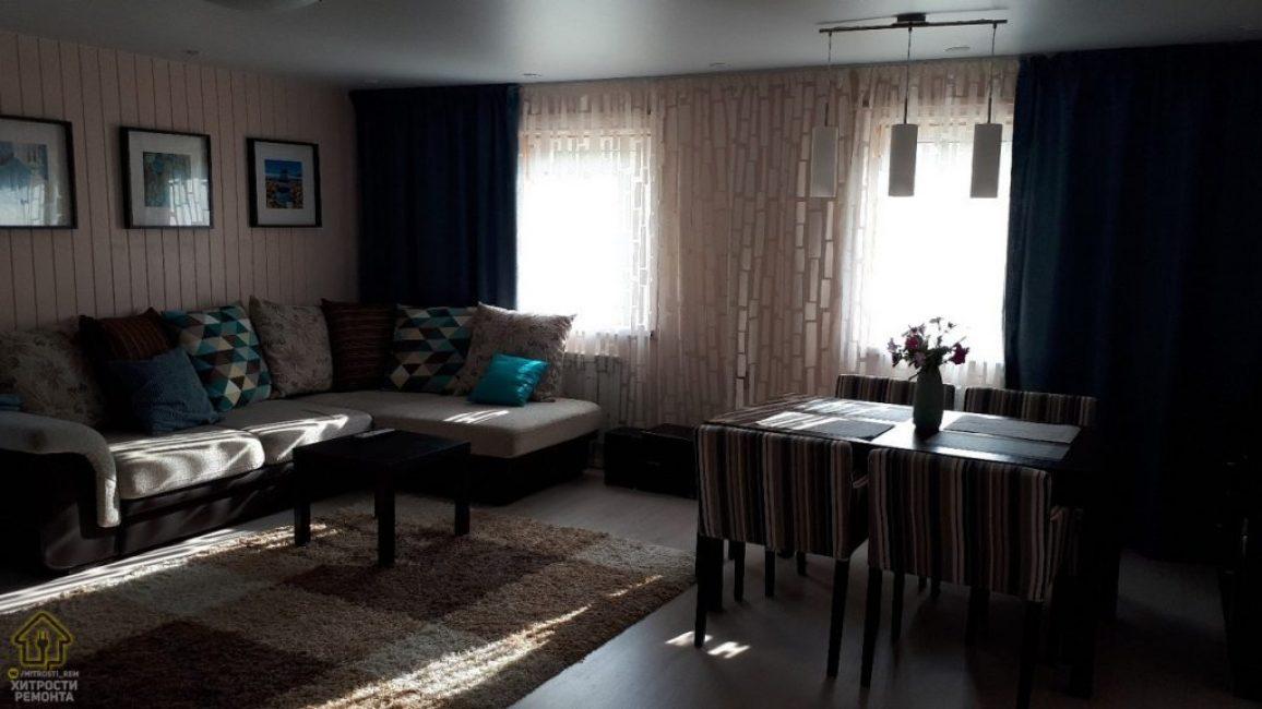 Несмотря на то, что практически все в гостиной светлых оттенков, в комнате довольно темно. В угол поставили диван декоративными подушками. На стену повесили три тематические картины.