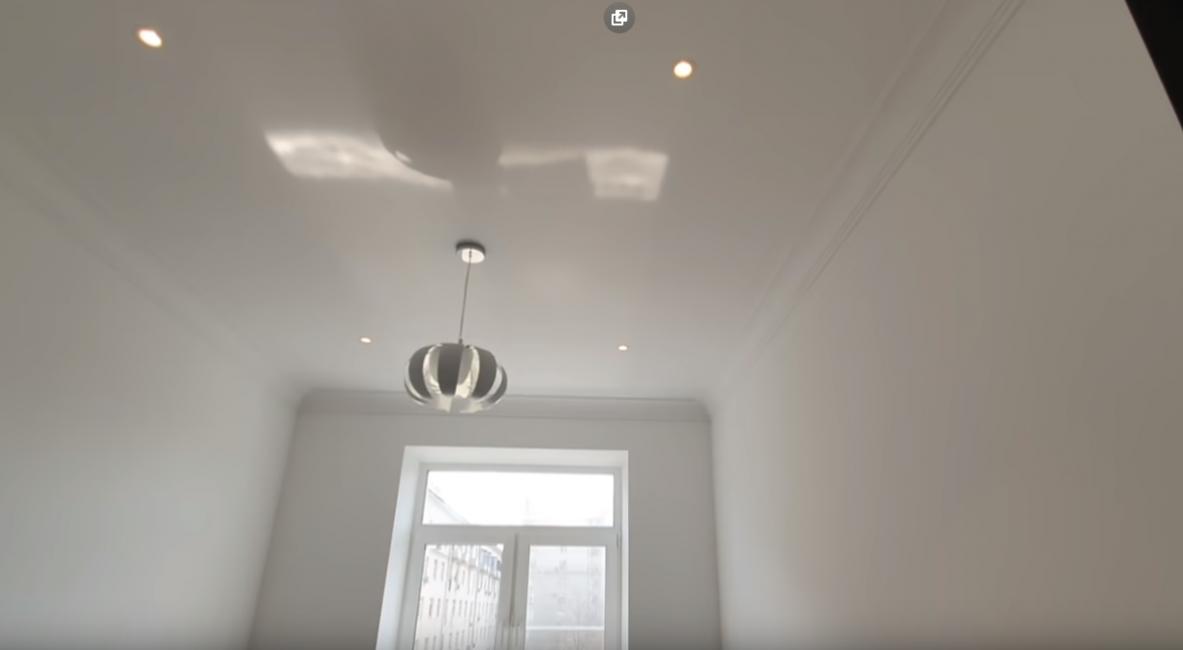 На потолке новая гипсовая лепнина. Сам потолок натяжной, со встроенными светильниками и белой люстрой.