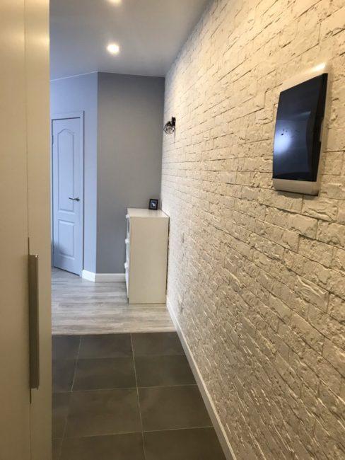 В коридоре стенку выложили белым декоративным кирпичом, а пол — темной коричневой плиткой. Достаточно практичный ход.