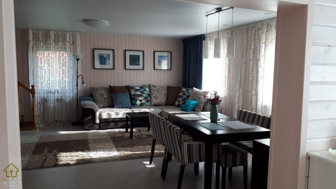 Освещением в комнате служит большая люстра в центре потолка. Также подвесной светильник с тремя плафонами над обеденным столом. Встроенные точечные светильники, расположенные оп периметру комнаты. Возле дивана стоит торшер для чтения.