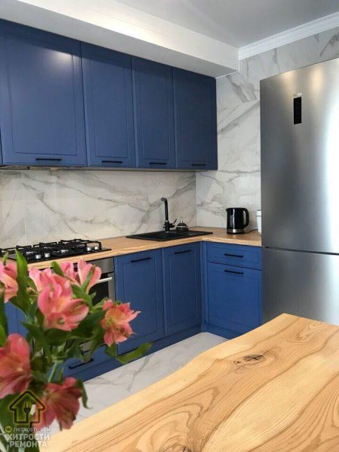 Кухонный гарнитур выбрали насыщенного синего цвета. Фартук и стены выложили светлой плиткой под мрамор. Обеденный стол и столешницу сделали под светлое дерево.