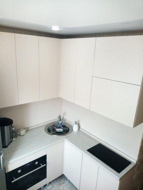 Кухонный гарнитур выглядит очень современно. Светлые фасады выполнены без ручек, поэтому они смотрятся одним цельным полотном в стиле модерн.