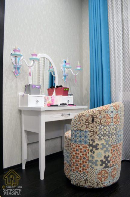 В комнате есть необходимый для каждой принцессы будуарный столик. Он выполнен в белом цвете и дополнен большим овальным зеркалом. По бокам для освещения повесили радужные бра. К столику приставили кресло, сделанное в стиле печворк.
