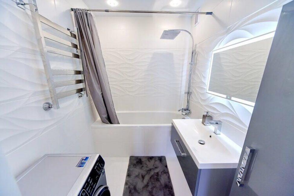 Ванная комната выполнена в белом кафеле. Использовался как гладкий, так и фактурный вариант. Комната сделана с акцентом на геометрические формы. Угловатость и линейность прослеживается в каждой детали, даже, в полотонцесушителе.