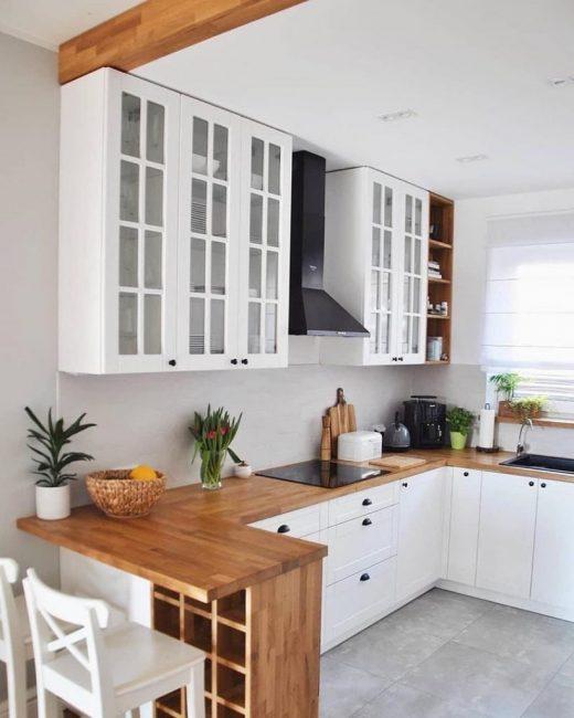 Кухонный гарнитур сделан в двух цветах: белом и цвете натурального дерева. С ним отлично перекликается деревянная балка на потолке.