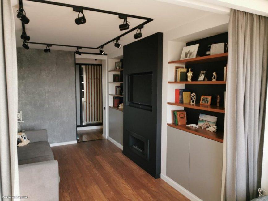 В зале есть черная стена, которую покрасили матовой краской. В ней есть ниша для плазменной панели, а ниже расположен камин.