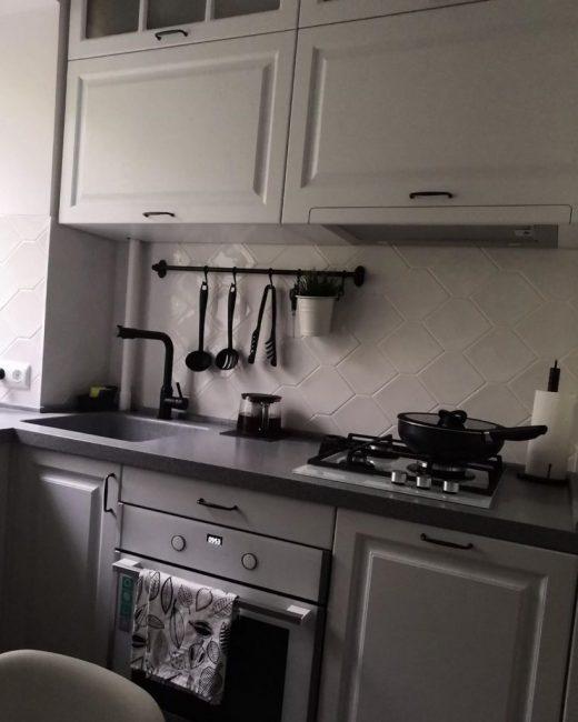 На керамогранитной рабочей поверхности серого цвета есть плита на три конфорки. Электрическая духовка также имеется, как и небольшая мойка.