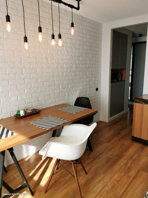 Обеденный стол длинный, рядом с ним черный и белый стул. На потолке лампочки на черной трубе — более лофтового светильника сложно придумать.