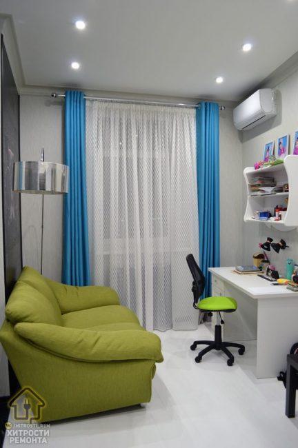 Окно украсили белым прозрачным тюлем в мелкий рисунок и плотными шторами яркого синего цвета. На стену повесили кондиционер.
