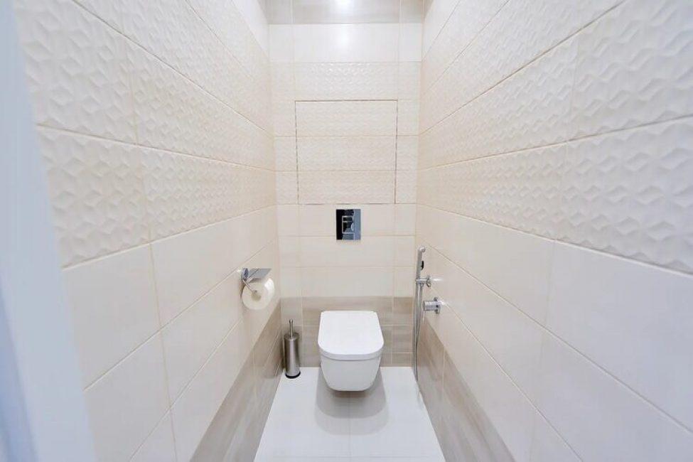 Туалет предельно простой, выложен светлой плиткой персикового оттенка. Сам унитаз подвесной. нагромождать туалет полками не стали.