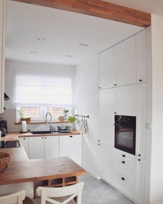 Электродуховка встроена в стенку. Рядом находится множество шкафчиков, в которых удобно хранить посуду и другую кухонную утварь. Холодильник решили также сделать встроенным, чтобы он не портил общую картину дизайна.