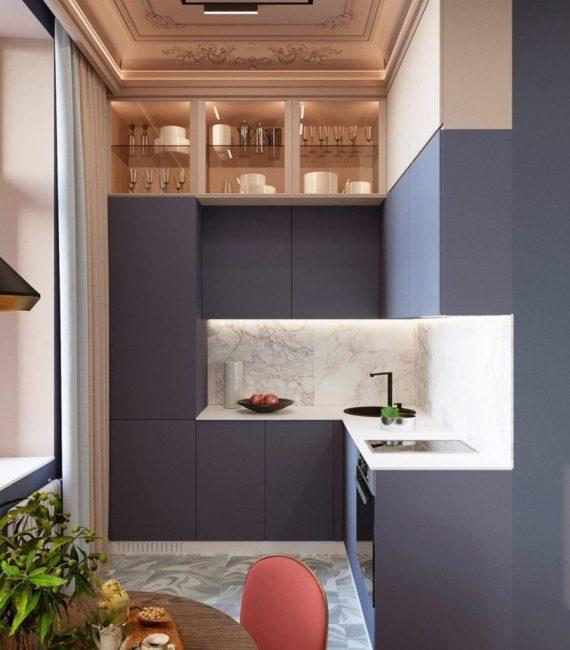 Мебель очень необычная. Если обеденные стулья были кирпичного цвета, то кухонный модуль голубого, с фиолетовым оттенком. Фартук выложили из белой плитки под мрамор.