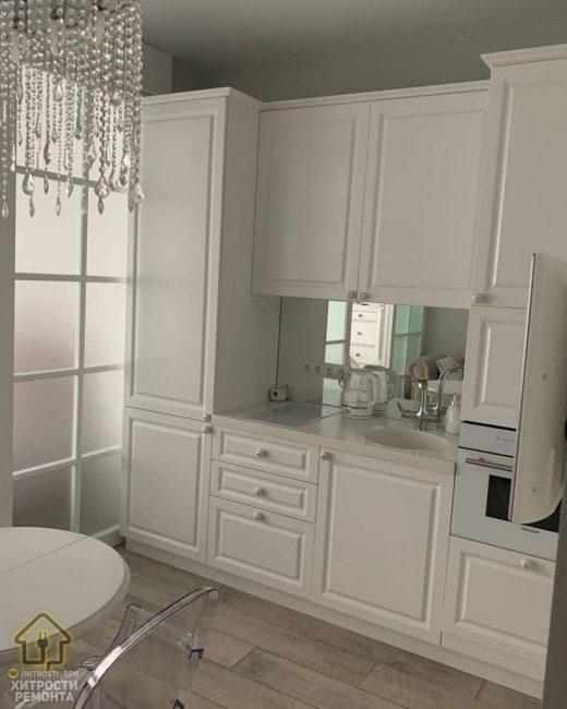 Кухонный гарнитур белоснежного цвета. Небольшая индукционная плита на две конфорки, рядом — мойка. Также есть электрический духовой шкаф. А вот на рабочую поверхность места не осталось.
