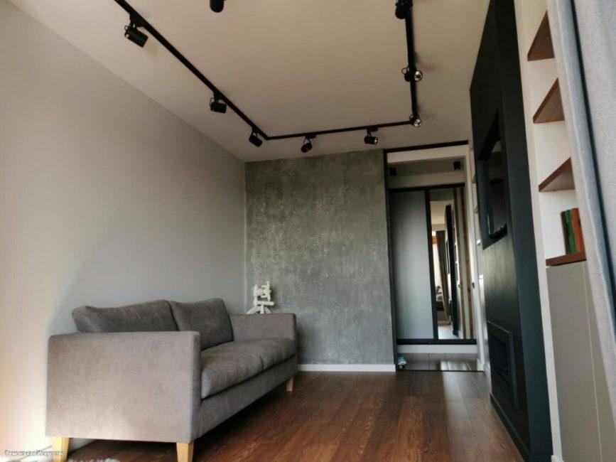 Потолок украшают уникальные черные светильники, которые расположены по периметру. Они мобильные, плафоны можно поворачивать в разные стороны.