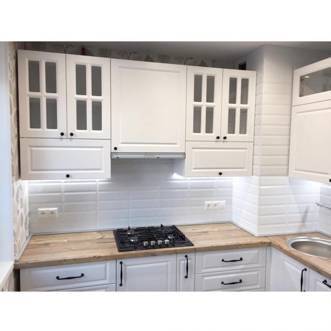 Фартук на кухне также белоснежный, имитирует глянцевый декоративный кирпич. Варочная поверхности черная, с четырьмя газовыми конфорками.