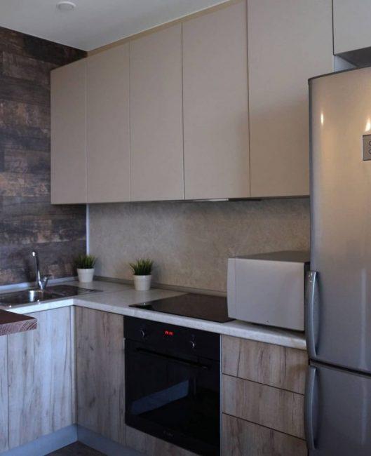 Кухонный гарнитур двухцветный. Верхние ящики бежевого цвета, без ручек. Нижние фасады также без ручек, сделаны под дерево. Столешница из светлого керамогранита. Фартук сделан под мрамор.