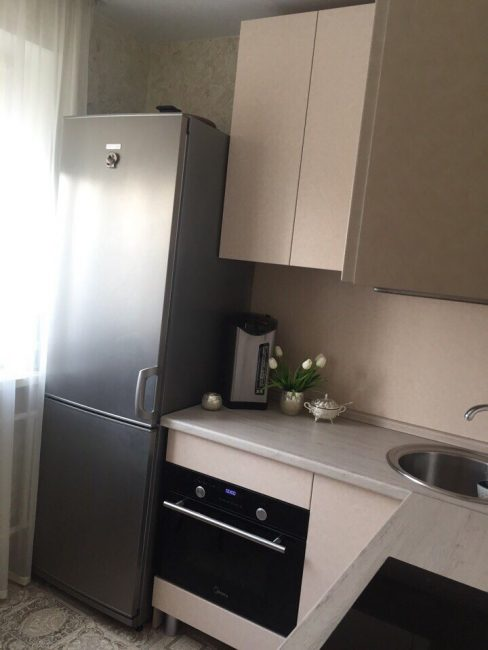 Темно-серый холодильник решили не прятать в кухонный гарнитур, так как это существенно удорожало ремонт. Рядом с холодильником расположилась встроенная духовка.