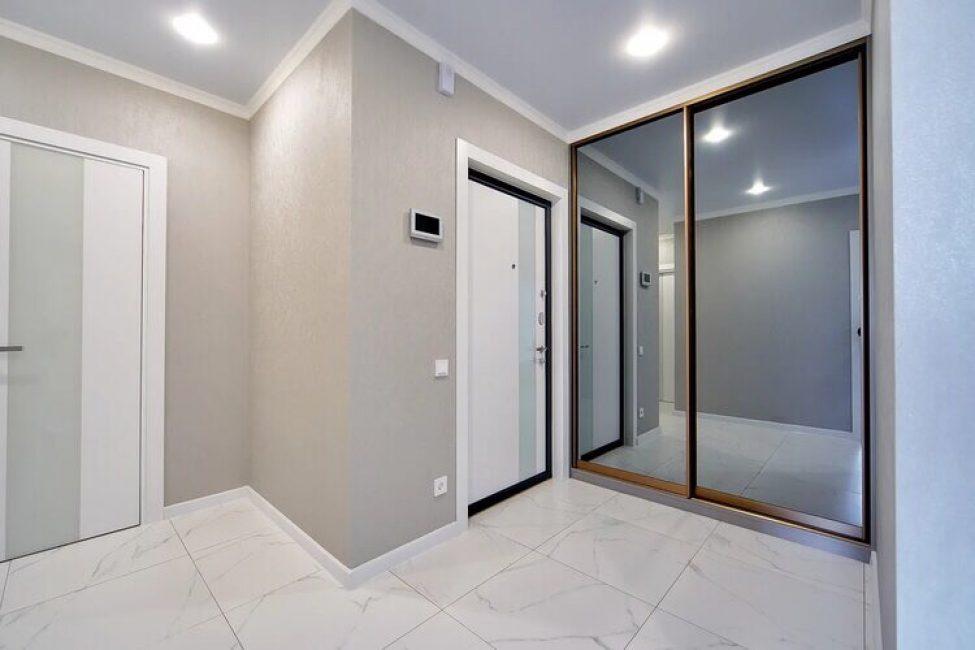 Коридор также сделали в светлых тонах. На стенах — кофейные обои, на полу — крупная белая плитка под мрамор. В углу соорудили большой шкаф-купе с зеркальными дверцами.