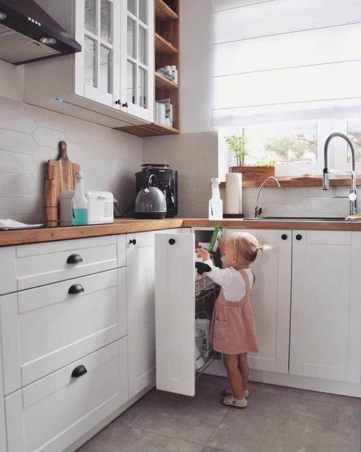 В кухонном гарнитуре также есть куча полок и шкафчиков. Рабочая поверхность сделана под натуральное дерево, а фартук выложен красивой белоснежной плиткой.