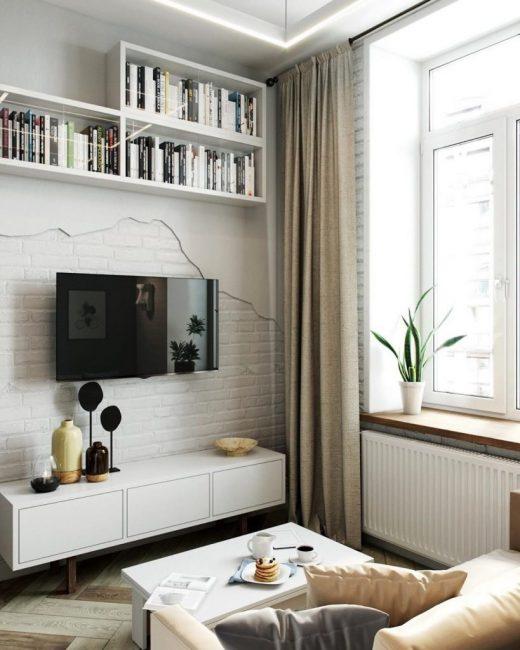 Зона отдыха, она же гостиная, представляет собой небольшой диванчик, напротив которого висит плазменная панель. Над ней расположились ряды книг на белых полках.