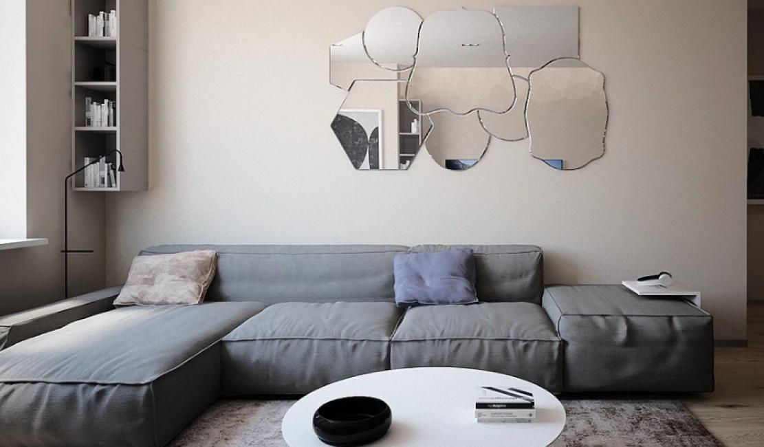 На стену за диваном повесили необыкновенную композицию из зеркал разных форм и размеров.