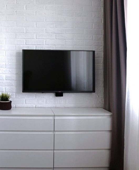 Напротив дивана повесили плазму, провода от которой замаскировали за белым декоративным кирпичом. Под телевизором разместился широкий комод.