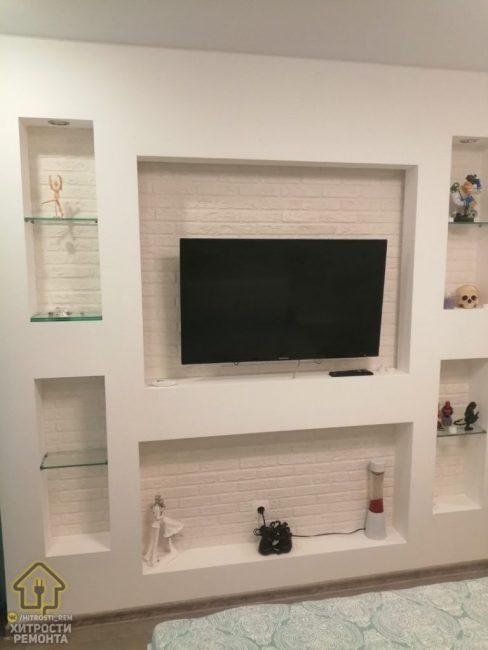 Напротив кровати собрали гипсокартоновую стенку с нишей для телевизора. Саму стенку отделали гипсовым декоративным кирпичом и покрасили в белый цвет.