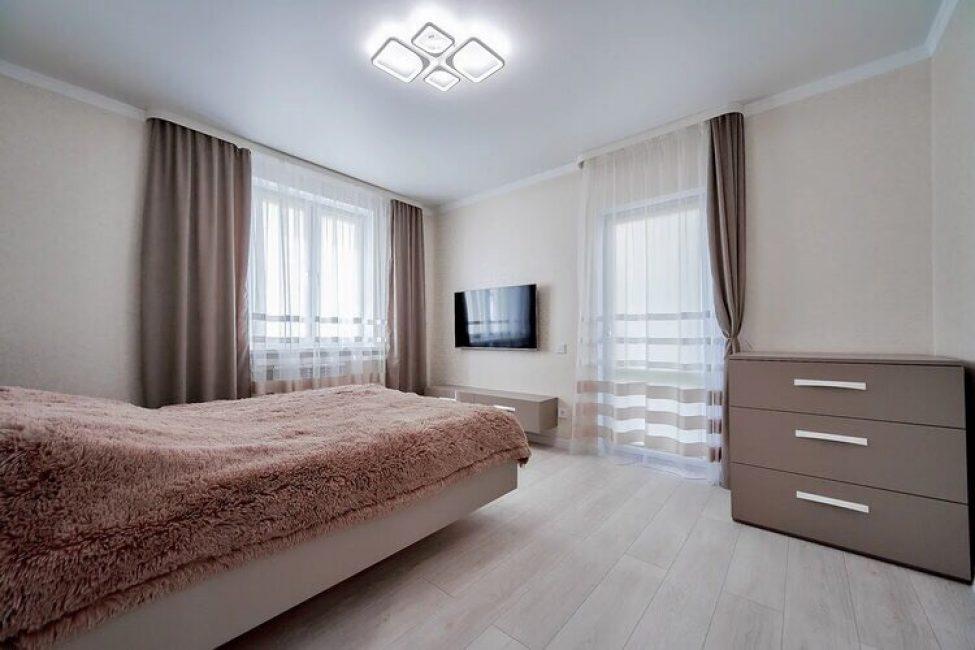 Спальня не белоснежная, в ней преобладают персиковые и кофейные оттенки. На пол положили ламинат, на окна повесили тюль и плотные шторы. Кроме большой двуспальной кровати в комнате есть комод, телевизор и тумба.