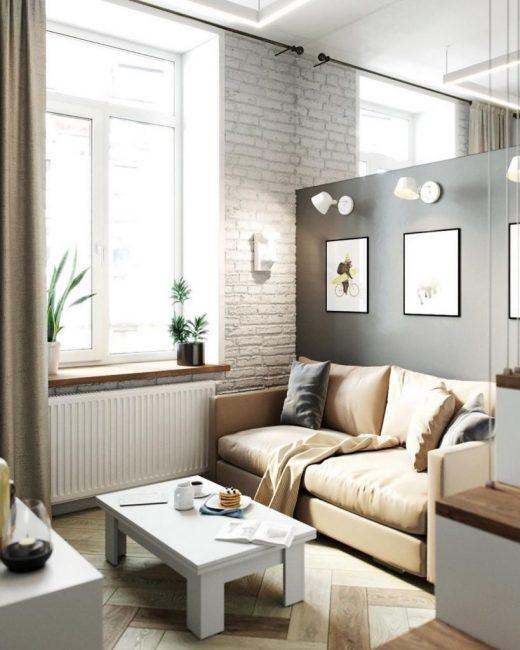 У дивана поставили белый кофейный столик. За диваном — черная перегородка, на которой висит три светильника и три картины.