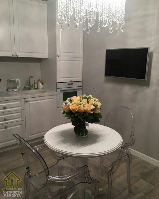 На стену повесили плазму с диагональю 32. Обеденная зона — это белоснежный круглый стол и два стула из прозрачного пластика. Над столом повесили люстру со стеклянными подвесами.