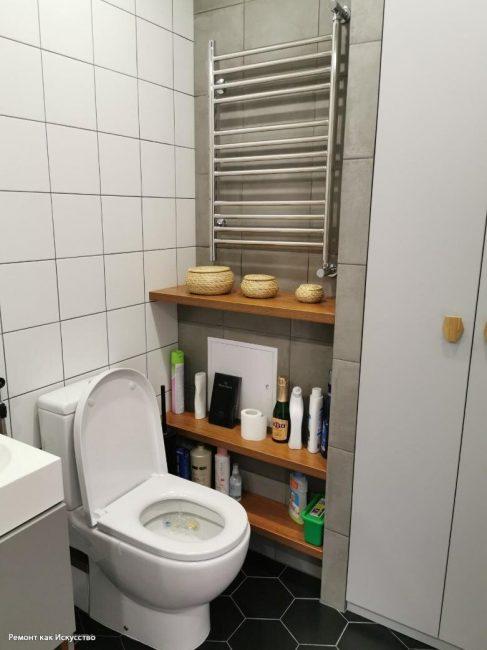 """Ванную комнату решили не перегружать. Стены выложили квадратной плиткой среднего размера, а на пол положили черную плитку """"соты"""" с белой затиркой."""