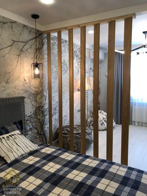 Зону спальни отделяет деревянная перегородка. По бокам кровати повесили светильники в стиле лофт.