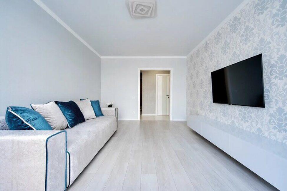 В этой комнате находится минимум мебели. Это всего лишь большой диван и плазменная панель на стене напротив. Под телевизором разместили белоснежную тумбу в стиле модерн.