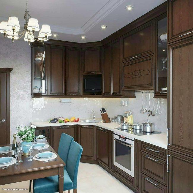Кухонный гарнитур выполнен из дерева насыщенного шоколадного оттенка. Рабочая поверхность белая. Варочная поверхность индукционная, духовка и холодильник встроенные.