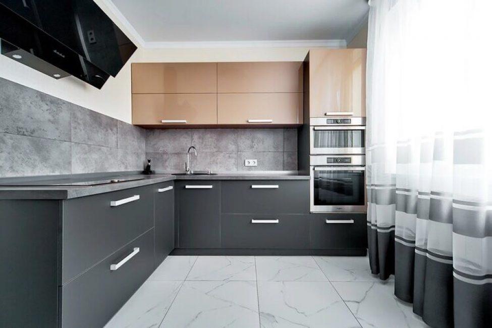 В продолжение прихожей, на кухне на пол положили такую же плитку под мрамор. Фартук выложили из серой плитки, имитирующей бетон.
