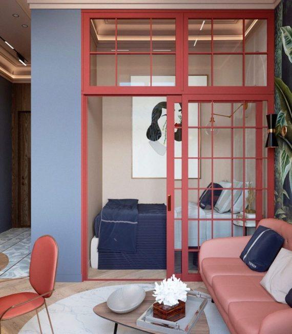 Зона для сна отделена раздвижными стеклянными дверьми. В небольшой образовавшейся комнатке стоит кровать и прикроватная тумбочка с лампой, а также висит картина в стиле модерн.