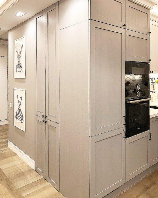 Холодильник и практически вся остальная техника в кухне — встроенная. Стену украшают оригинальные постеры в рамках.