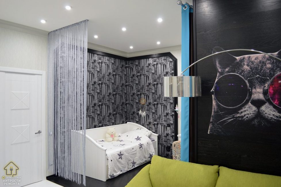 На стену за диваном наклеили постер с изображением кота. Спальную зону выделили другими отделочными материалами, встроенными точечными светильниками и ниточной шторкой.